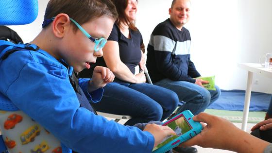 Fiúgyermek kommunikációs segédeszköz, tablet használata közben