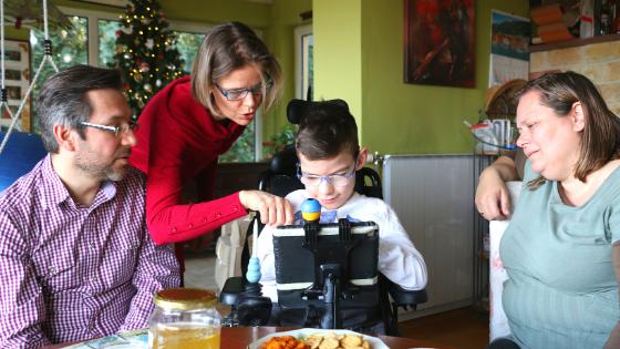 Fiúgyermek kommunikációs segédeszközzel ismerkedik, körülötte a szülei