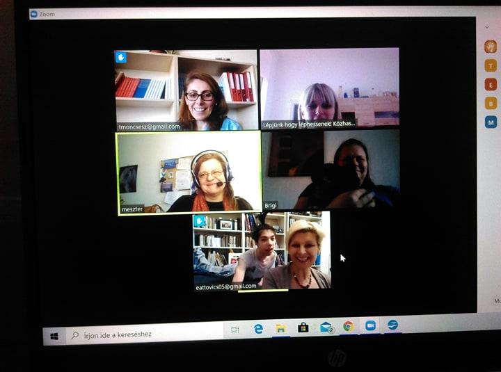 Online értekezlet a kommunikációs segédeszközök támogatásáról öt mosolygós résztvevővel és egy megfigyelő fiúval.